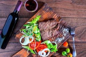 steak et légumes sur une planche à découper photo