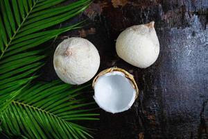 noix de coco et feuilles de palmier sur une table en bois