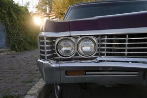 Phare et vue avant des détails d'une voiture classique violette dans la rue photo