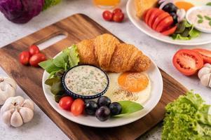 croissant, œuf au plat, vinaigrette, raisins noirs et tomates