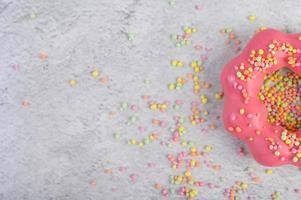 un demi-beignet aux fraises décoré de glaçage et de pépites