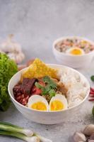 Repas thaï au yentafo avec œuf à la coque, oignon nouveau, piment, citron vert et ail photo