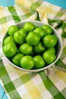 Prunes vertes aigres dans un bol blanc sur tissu à carreaux photo