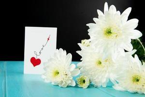 Chrysanthèmes blancs et une carte postale sur un fond en bois bleu photo