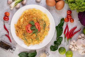 omelette sur une assiette blanche avec des tomates
