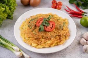 Omelette aux œufs sur une assiette blanche avec des tomates