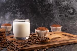 lait dans un verre avec grains de café et muffins