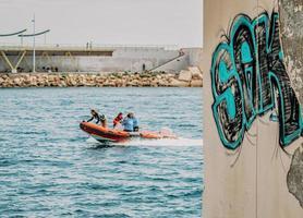 2 personnes à cheval sur un bateau bleu et blanc pendant la journée photo