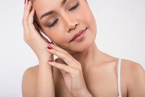 jeune femme touchant ses joues sur fond blanc photo