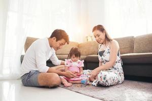 enfant avec ses parents jouant sur le sol à la maison photo