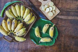 bananes fraîches dans un panier sur une table en bois photo