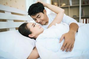 couple heureux allongé ensemble dans leur lit photo
