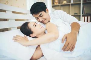couple heureux allongé ensemble dans leur lit