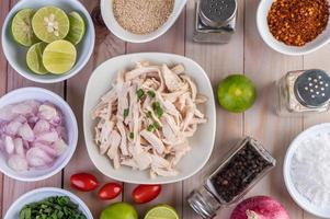 Morceaux de poulet bouilli avec légumes et épices sur une table en bois