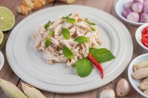salade de poulet sur une assiette blanche avec des feuilles de menthe