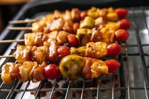 barbecue avec une variété de viandes, tomates et poivrons