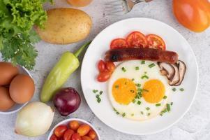 assiette petit-déjeuner avec œufs au plat, tomates, saucisse chinoise et champignons