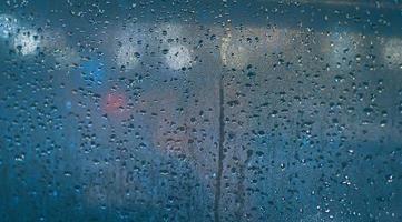 gouttes de pluie sur la vitre de la voiture. flou abstrait bokeh du trafic et de la lumière de la voiture. photo
