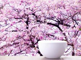 maquette de tasse blanche vierge sur table en bois. branches d'arbres frais avec des feuilles vertes flou fond