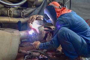 le soudeur assemble la valve à la canalisation photo