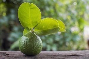 citron vert frais avec des feuilles sur fond de bois