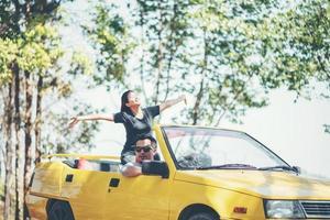 couple heureux profitant du toit en cabriolet photo