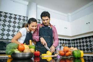 heureux, jeune couple, préparer, nourriture, pour, cuisine, dans, cuisine, chez soi photo