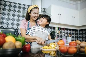 heureuse maman et fille préparer et hacher des légumes dans la cuisine photo