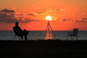 un homme photographe regardant le soleil photo