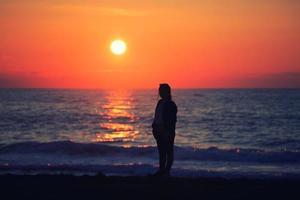 une femme photographe regardant le coucher du soleil photo