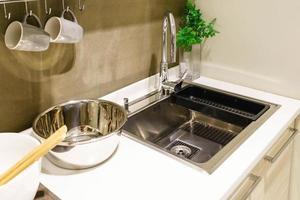 cuisine blanche moderne avec appareils électroménagers en acier inoxydable et plan de travail en granit