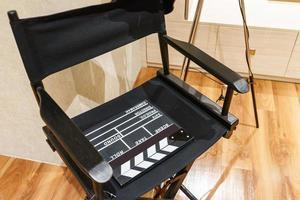 Chaise de réalisateur, battant de film et mégaphone dans la lumière volumétrique sur fond de bois. photo