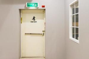 Sortie de secours du bâtiment avec panneau de sortie sur la porte et extincteur à l'extérieur d'un bâtiment photo
