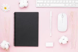 table de bureau minimaliste avec ordinateur clavier, souris, stylo blanc, fleurs de coton, gomme sur une table pastel rose avec espace de copie pour saisir votre texte, composition du lieu de travail de couleur rose, pose à plat, vue de dessus photo