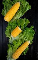 Vue de dessus du maïs cuit entier et coupé avec de la laitue sur fond noir