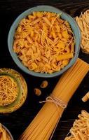 Vue de dessus de différents types de macaronis comme spaghetti vermicelles tagliatelles et autres sur fond de bois photo