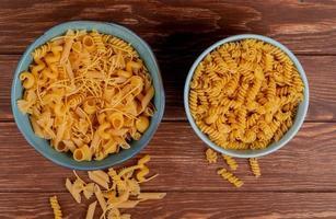 Vue de dessus de différents macaronis et rotini macaronis dans des bols et sur fond de bois photo