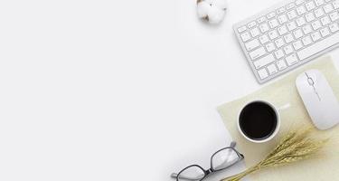 Vue de dessus de table de bureau minimal avec ordinateur clavier, souris, lunettes, plante de riz tasse à café, sac sur une table blanche avec espace de copie, composition du lieu de travail de couleur blanche, pose à plat photo