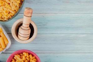 Vue de dessus de différents types de macaronis comme ziti fusilli et autres avec des graines de poivre noir dans un broyeur d'ail sur fond de bois avec espace de copie photo