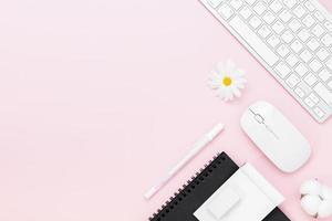 Vue de dessus de table de bureau minimal avec ordinateur clavier, souris, stylo blanc, feuille de monstera, fleurs de coton, verres sur une table rose avec espace copie, photo
