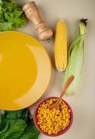 Vue de dessus des graines de maïs cuites avec épis de maïs épinards et laitue avec assiette vide sur fond blanc photo