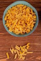 Vue de dessus de différents macaronis dans un bol et sur fond de bois photo