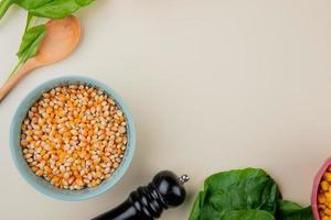 Vue de dessus du bol de graines de maïs aux épinards et cuillère en bois sur fond blanc avec copie espace