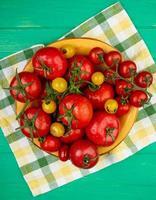 Vue de dessus des tomates dans un bol sur un tissu sur fond vert