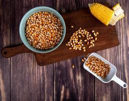 Vue de dessus du bol de graines de maïs maïs coupé sur une planche à découper avec une cuillère pleine de graines de maïs sur fond de bois photo