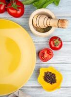 Vue de dessus des légumes comme des feuilles de menthe verte tomate avec des graines de poivre noir broyeur d'ail et assiette vide sur fond de bois photo