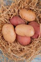 Vue de dessus des pommes de terre blanches et rouges au nid sur fond de bois photo