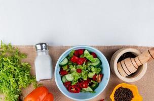 Vue de dessus de la salade de légumes avec bouquet de coriandre poivre sel poivre noir graines sur un sac et fond blanc avec copie espace photo