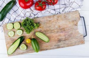 Vue de dessus des légumes comme concombre tomate coriandre sur planche à découper avec concombre et tomates sur tissu et fond en bois photo
