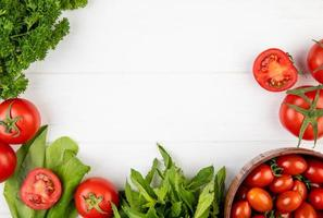 Vue de dessus des légumes comme la coriandre tomate épinards feuilles de menthe verte sur fond de bois avec espace copie photo